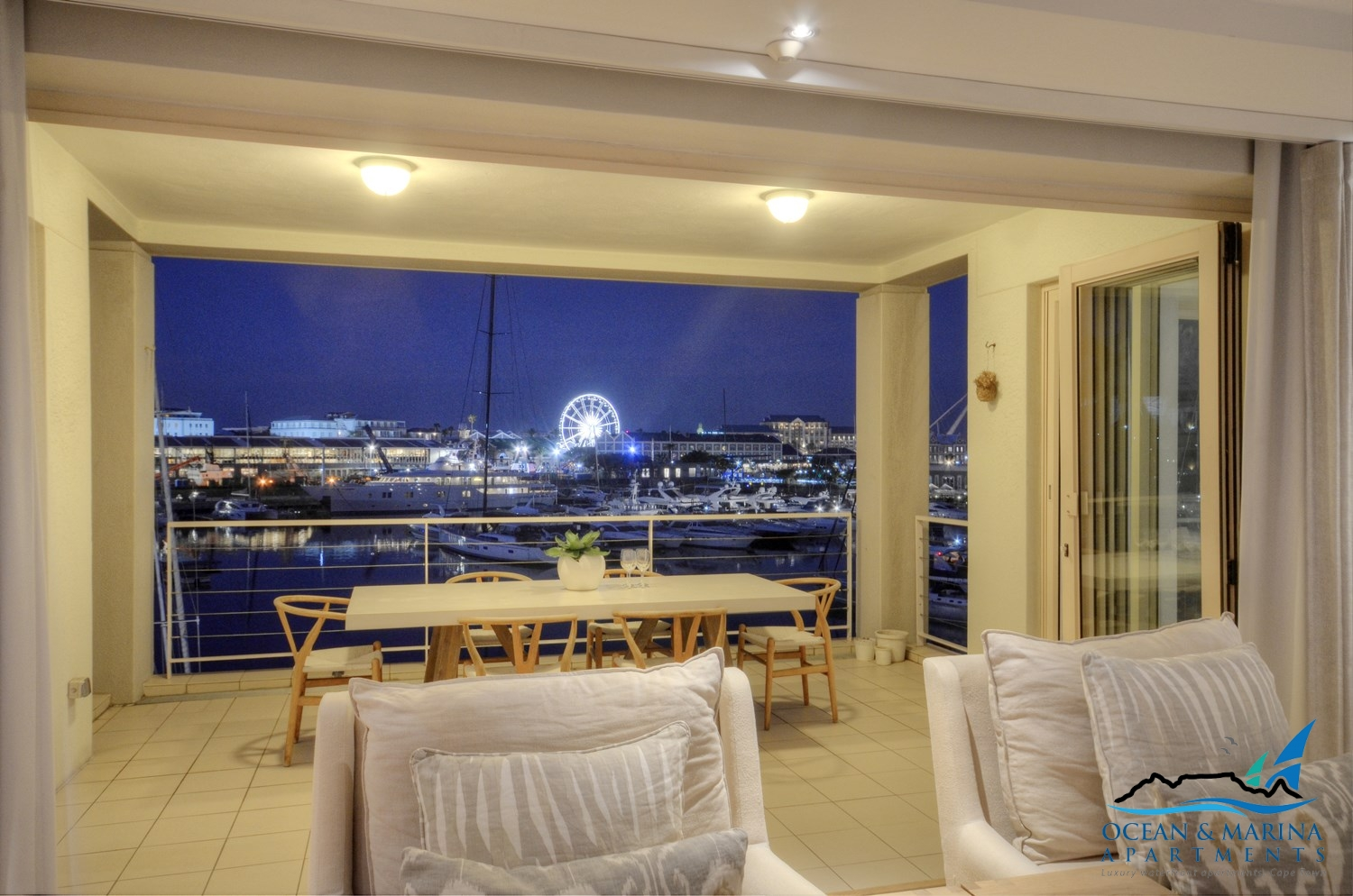 Penrith Apartment living area with a nighttime waterfront & marina view.